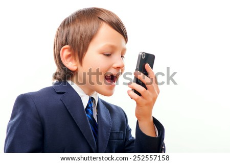 Little businessman. Confident little boy in suit talking emotionally on the phone while standing isolated over white background - stock photo