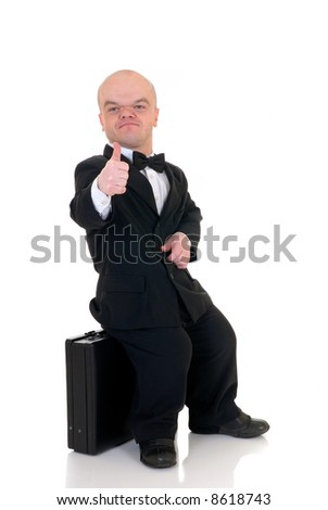 Little businessman, dwarf in a formal suit with bow tie next to  suitcase, studio shot, white background