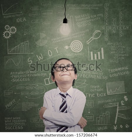 Little businessman looking at lit bulb with drawn formula on the board - stock photo