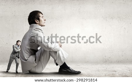 Little businessman trying to move the giant one - stock photo