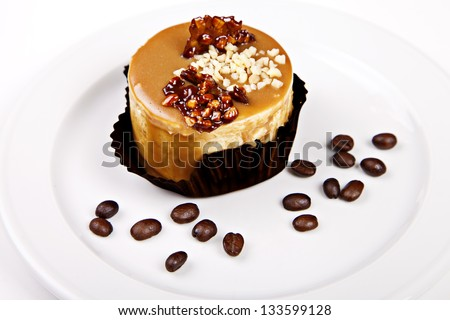 Little cake with caramel and nuts on white background
