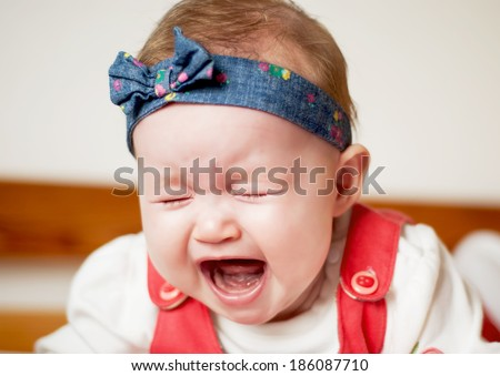 Little caucasian baby girl heart wrenching crying. - stock photo