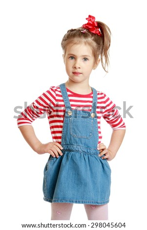 Little Caucasian blond girl in a short denim dress and red striped t-shirt looks straight into the camera , close-up-Isolated on white - stock photo