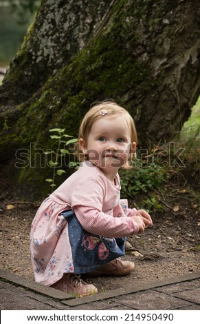 Little caucasian blond girl in beautiful dress kneeling on the ground. - stock photo
