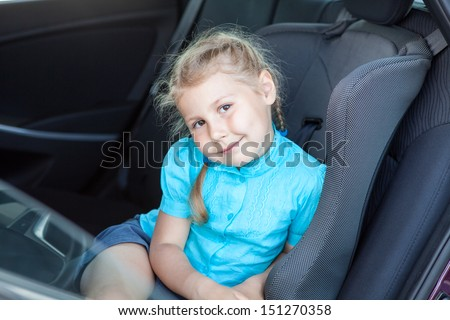 Little Caucasian blond girl in car safety seat going to journey - stock photo