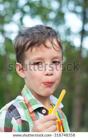 Little caucasian boy eating ice cream outdoor in summer. - stock photo