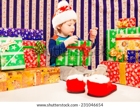 little caucasian boy in hat with Christmas gifts - stock photo