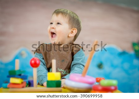 Little caucasian boy is smilling and Montessori toys - stock photo