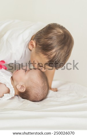 Little Caucasian Boy Kissing His Newborn Sister. Indoors Shot. Vertical Image - stock photo