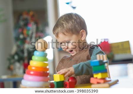 Little caucasian boy plaing with Montessori toy in pre-school - stock photo