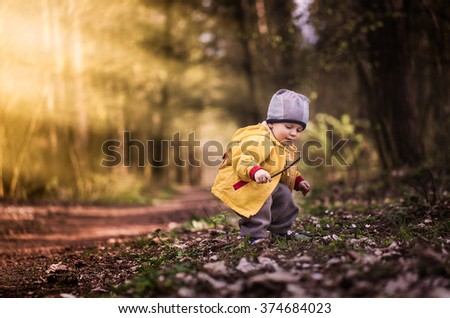 Little caucasian boy playing in springtime forest.