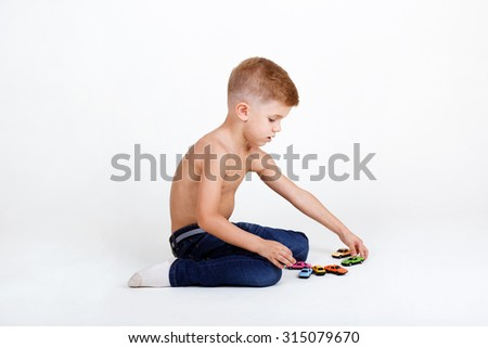 little caucasian boy plays with colorful toy cars - stock photo