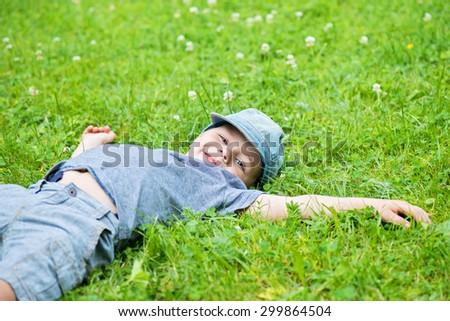 Little caucasian boy resting on green grass - stock photo