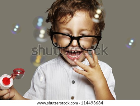 little caucasian boy with soap bubbles on grey background - stock photo