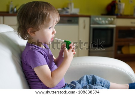 Little caucasian child using inhaler - stock photo