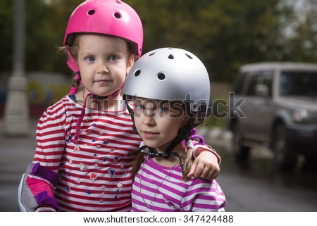 Little caucasian cute girls wearing a roller protection and helmets