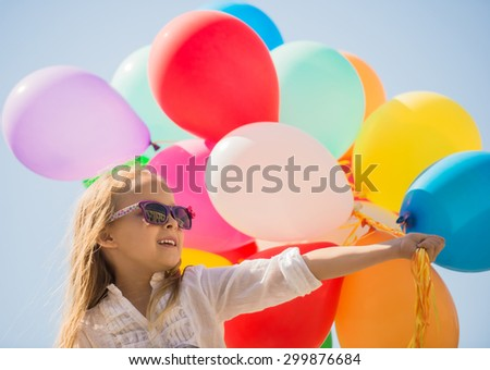 Little caucasian girl walking outdoor, holding a bunch of helium filled balloons. - stock photo