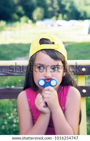 Little caucasian girl with Fidget Spinner held up to his lips outdoors. Crazy game of 2017.