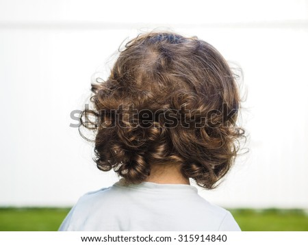 Little caucasian person with curly hair staring at watching a white wall - stock photo