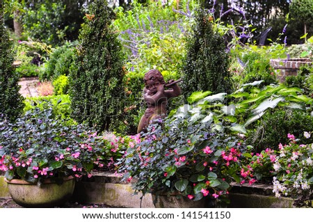 little ceramic statue of a faun playing the flute  in between colorful flowers - stock photo