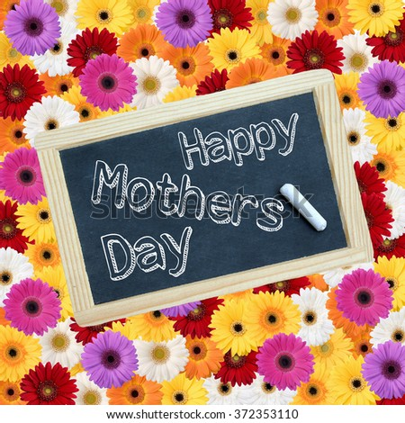 little chalkboard laying down on a background of flowers with the text words ; Happy mothers day  - stock photo