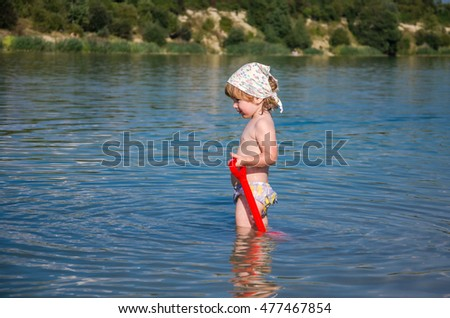 Little charming girl baby playing on the lake swimming in the water during vacation at the resort on a sandy beach