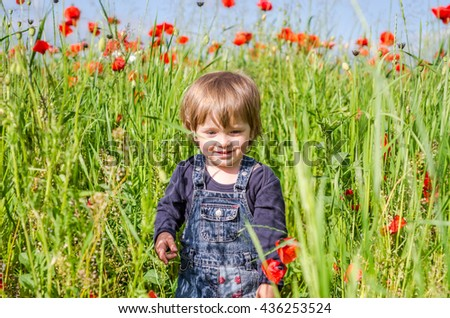 Little charming girl baby walking on the poppy field among the grass