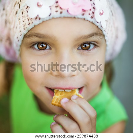 Little cheerful beautiful girl bites off tasty cookies in summer city park. - stock photo