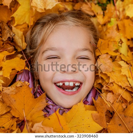 Little cheerful beautiful girl buried in autumn maple leaves yellow.