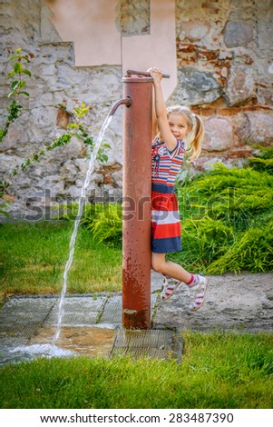 Little cheerful beautiful girl opens water tap in street.