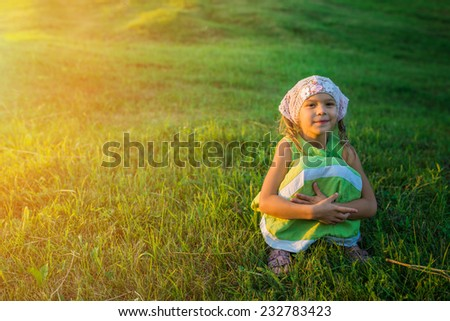 Little cheerful beautiful girl sitting on grass in summer city park.