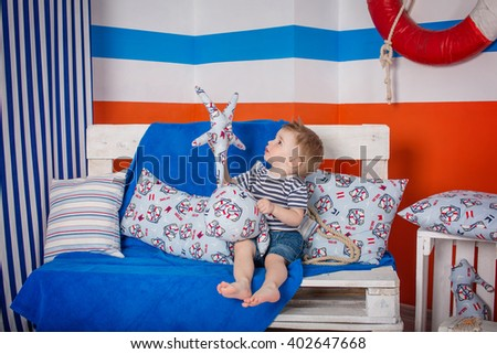 Little cheerful  boy in a striped T-shirt in the summer sea played with shells, lighthouse, sitting and standing barefoot in a bright color studio - stock photo