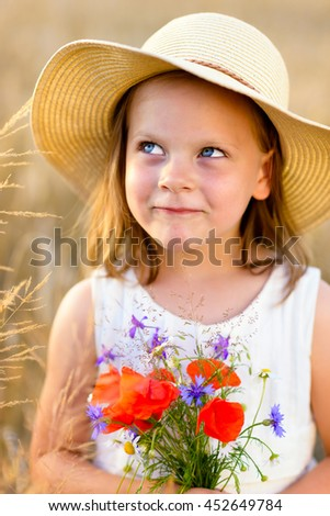 Little cheerful girl in a straw hat with wild flowers red poppy bouquet in the summer meadow - coquettish, mischievous face - stock photo