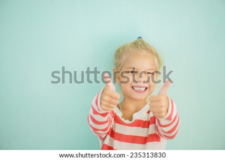 Little cheerful girl lifts thumb upwards, on green background. - stock photo