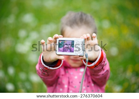 Little cheerful girl making a selfie with digital camera, enjoying her time on a dandelion meadow. Active lifestyle, curiosity, pursuing a hobby, technology and kids  concept.