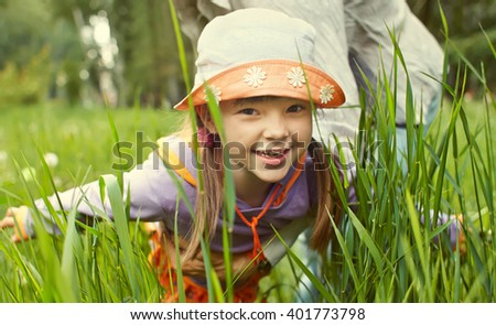 Little cheerful girl playing in the grass depicts a plane arms outstretched - stock photo
