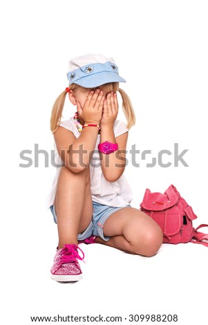 Little cheerful girl school girl in bright clothes covering her face her hands on a white background isolated - stock photo