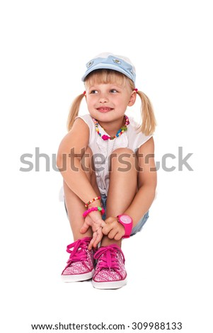 Little cheerful girl school girl in bright clothes on a white background isolated