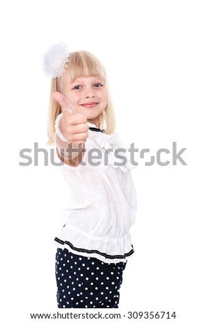 Little cheerful girl schoolgirl isolated on a white background with a raised thumb