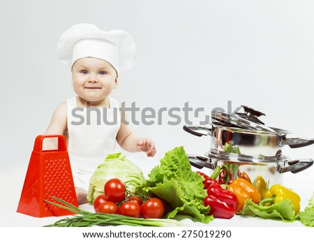 Little Chef boy preparing healthy food and looking and smiling in camera over white background. the concept of vegetarianism