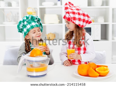 Little chef girls tasting the fresh orange juice they made - healthy nutrition concept - stock photo