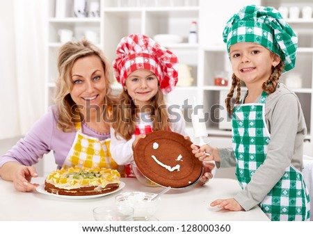 Little chef girls with their mother making a cake in the kitchen - stock photo