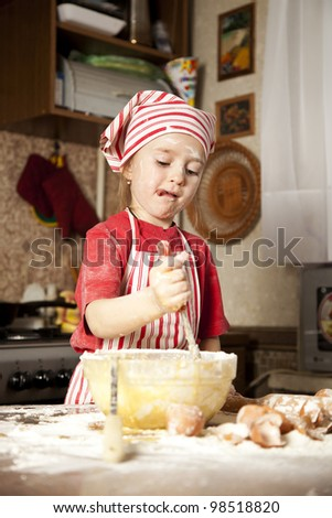 little chef in the kitchen wearing an apron and headscarf
