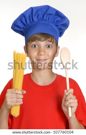 Little chef kid holding a bunch of crude spaghetti on white background.Little kid holding pasta. - stock photo