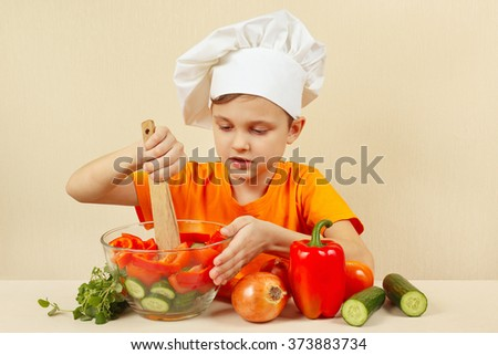 Little chef mixing the vegetables in a bowl with salad
