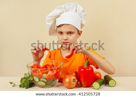 Little chef puts chopped vegetables for a salad in a bowl
