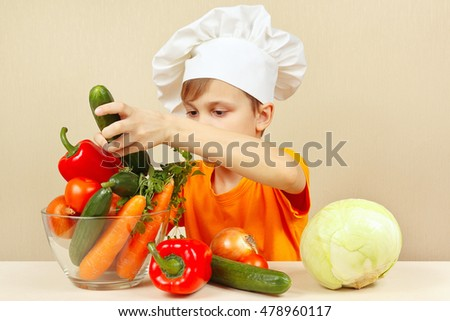 Little chef with vegetables at the table