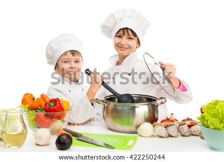 little chefs by table with vegetables in white uniform