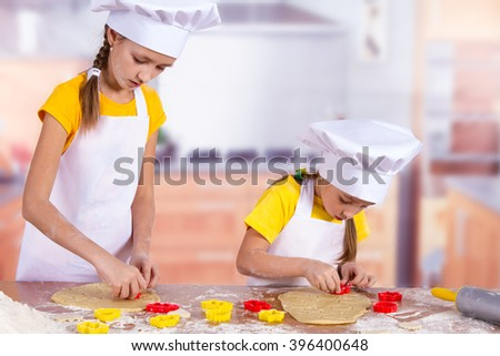 little chefs cook the biscuits, cut dough figurines biscuits - stock photo