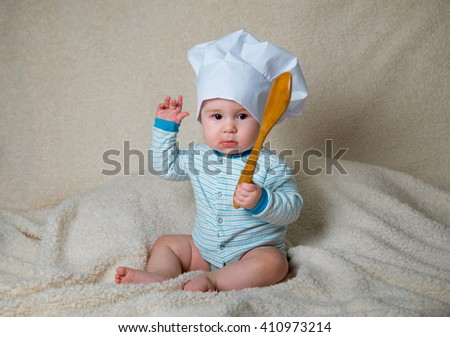 Little chief with a wooden spoon on a white furry background